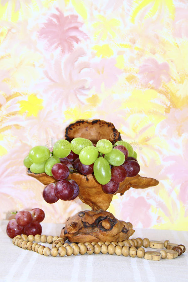 Exclusive wooden vase with pink and green grapes royalty free stock photography
