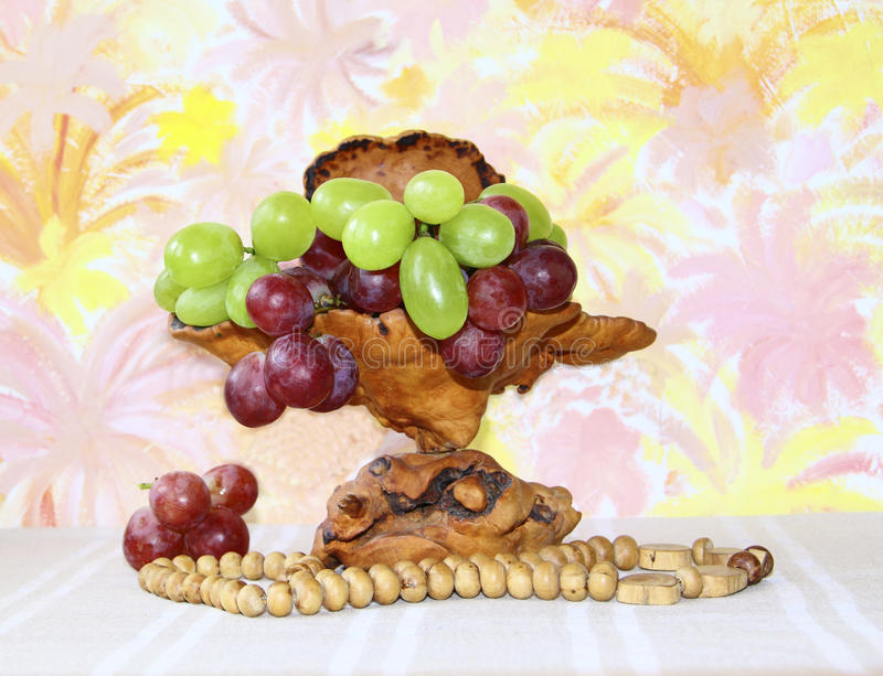 Exclusive wooden vase with pink and green grapes stock photo