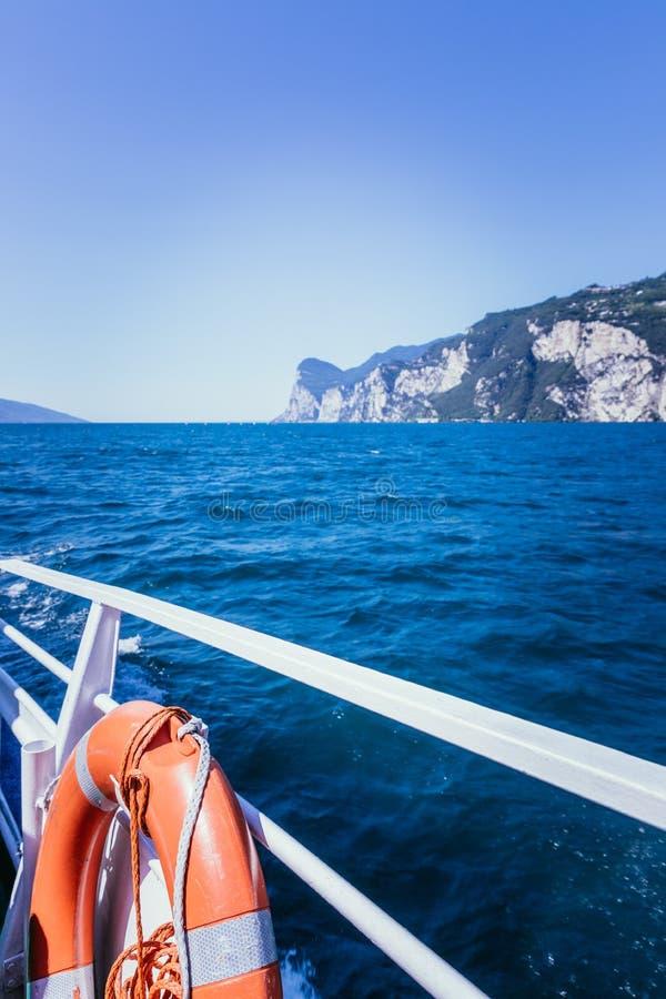 Excursão do barco: Trilhos do barco, vista sobre a água azul dos azuis celestes e cordilheira Lago di Garda, Italy foto de stock