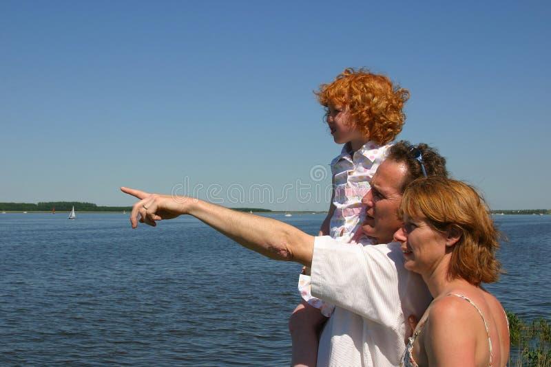 Excursión de la familia en la orilla del agua