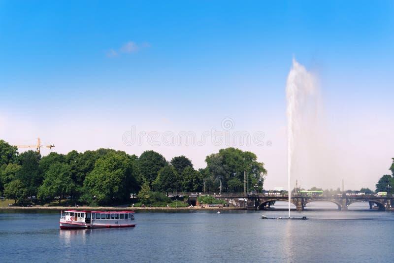 Excursieschip en een fontein op het Alster-meer als wereldberoemde oriëntatiepunten van de stadscentrum van Hamburg stock afbeeldingen