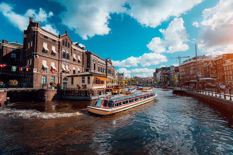 Excursion boat on the river Amstel. Cityscape of Amsterdam Netherlands. Amazing cloudscape on sunny autumn day. Vacation. Weekend in Europe stock photos