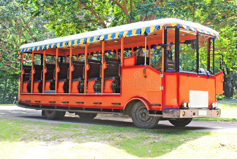 Excursion Bus. An open sided orange bus used for excursion parked under a tree lined dirt road royalty free stock photography