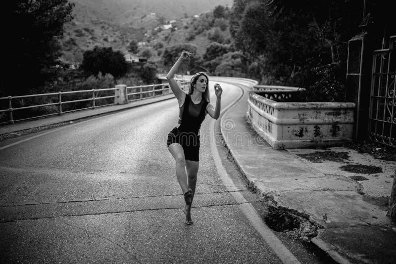 Executando a dança contemporânea no meio de uma estrada imagens de stock royalty free
