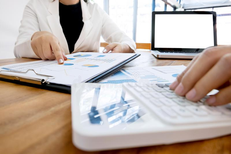 Executive analysis on data paper and accountant using calculator at the office with blank screen laptop, business concept.  stock photo