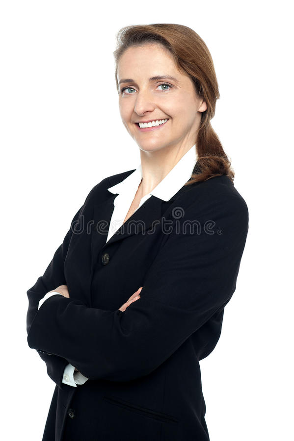 Executive in business suit standing arms folded. Pretty business executive posing sideways with folded arms on white background royalty free stock images
