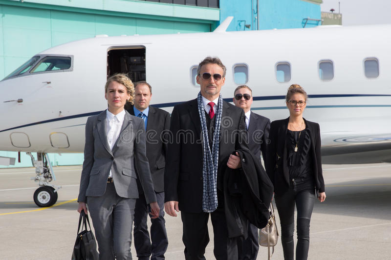 Executive business team leaving corporate jet. Executive manager leaving corporate jet and standing on the runway royalty free stock photos