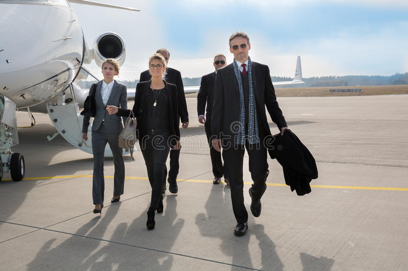 Executive business team leaving corporate jet stock images