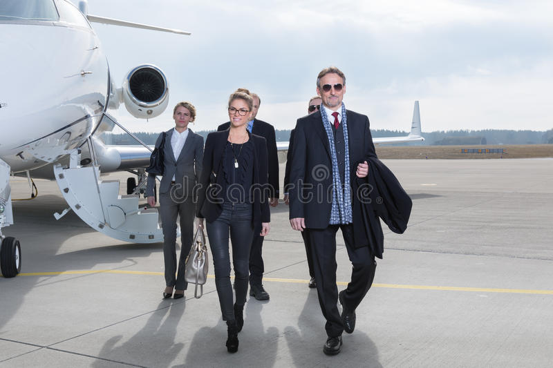 Executive business team leaving corporate jet stock photos