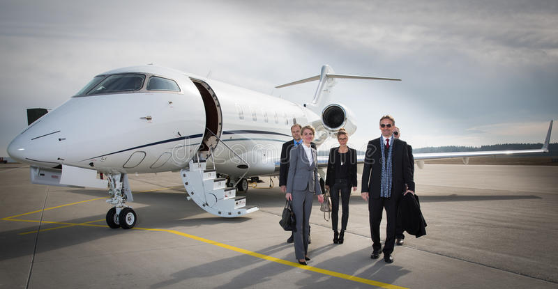 Executive business team leaving corporate jet. And walking towards camera stock images