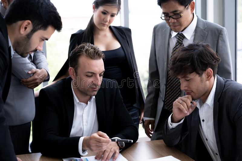 Executive businessman in group meeting with other businesspeople stock image