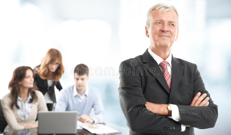 Executive businessman portrait. Executive businessman standing at office while business people working on laptop at background. Teamwork royalty free stock photography