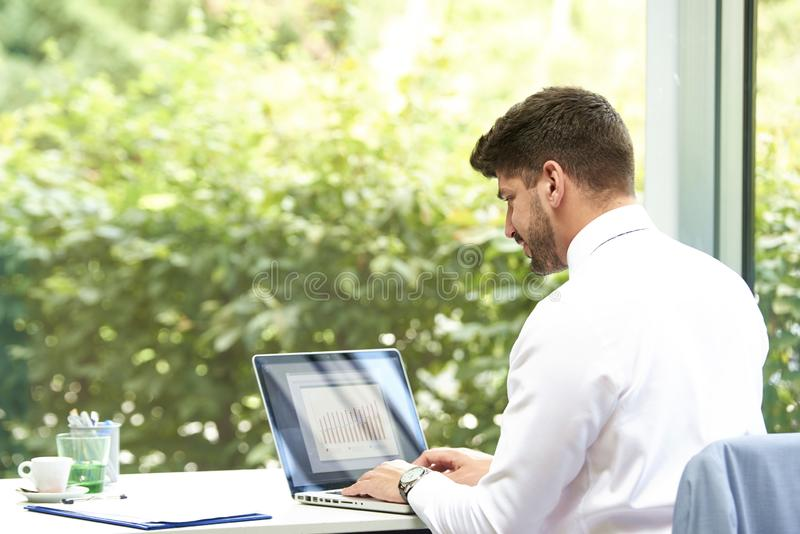 Executive businessman using notebook while working in the office stock image