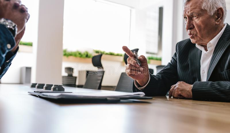 Executive explaining business contract to coworker royalty free stock photography