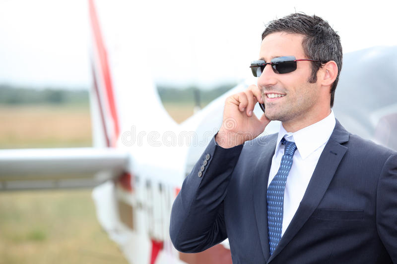 Executive in front of plane. Executive standing in front of his private plane