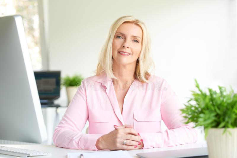 Executive marketing businesswoman sitting at the office royalty free stock image