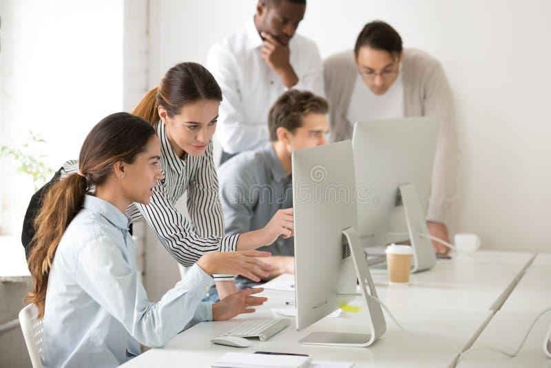 Executive mentor explaining young intern or new employee online. Executive mentor explaining intern or new employee online task pointing at computer screen stock photos