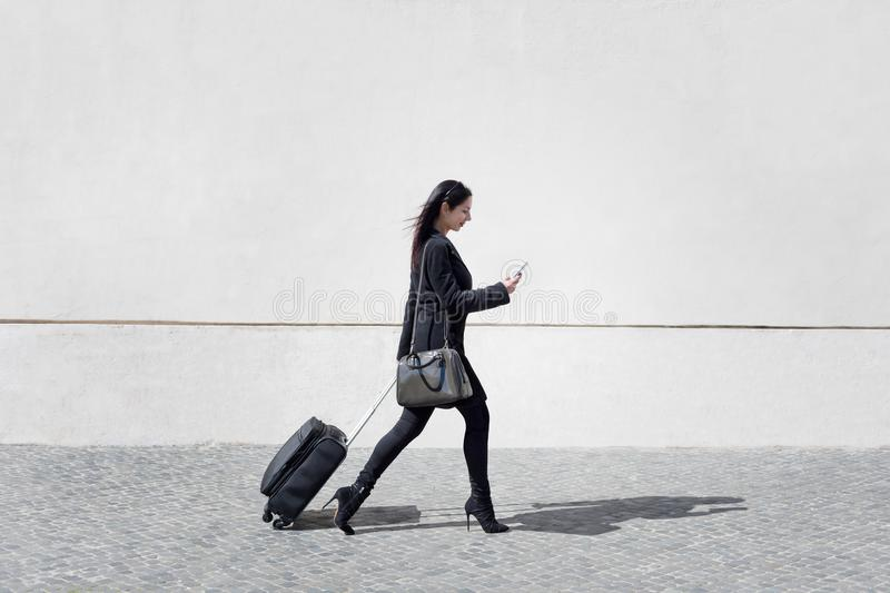 Executive and modern woman walks the street with her luggage while texting the mobile phone. stock photos