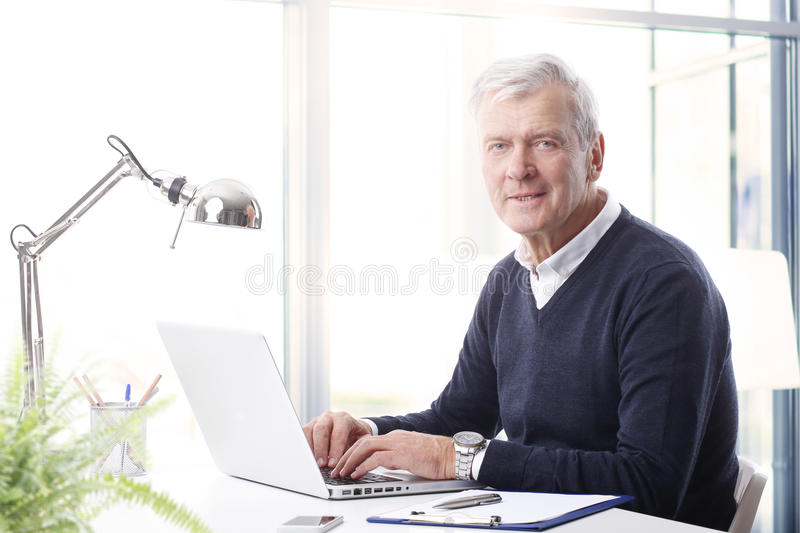 Executive officer portrait. Close-up portrait of handsome senior businessman using a laptop while looking at camera royalty free stock photo