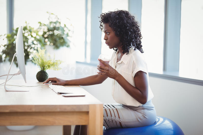 Executive sitting on fitness ball while working at desk. In office royalty free stock photos