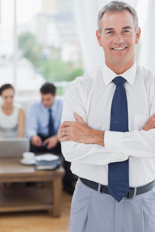Download Executive Standing On Foreground With Colleagues On Background Stock Photo - Image: 33052020