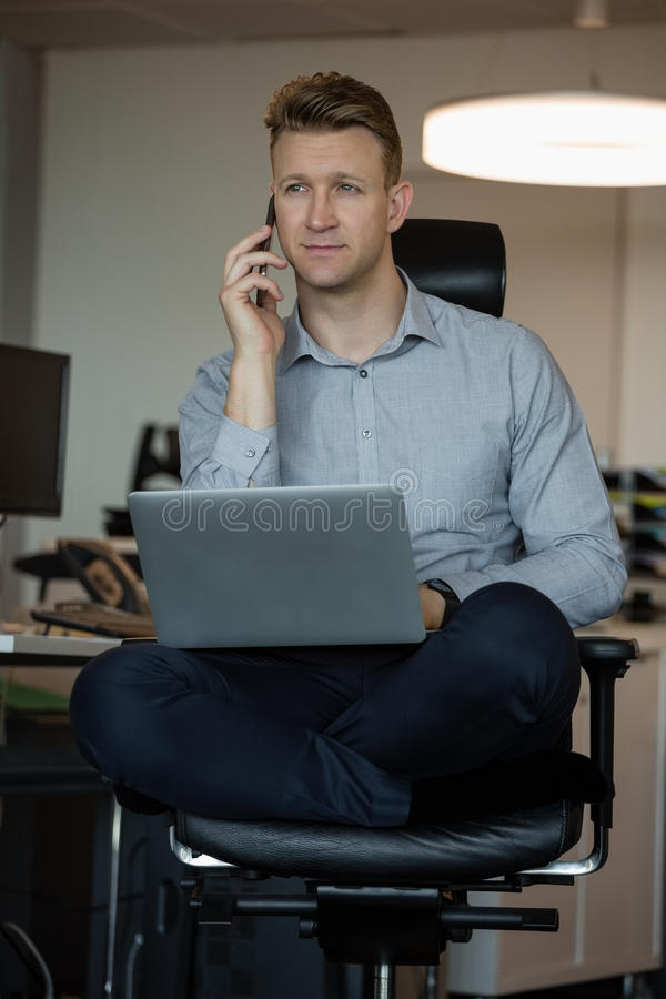 Executive talking on mobile phone while using laptop stock image