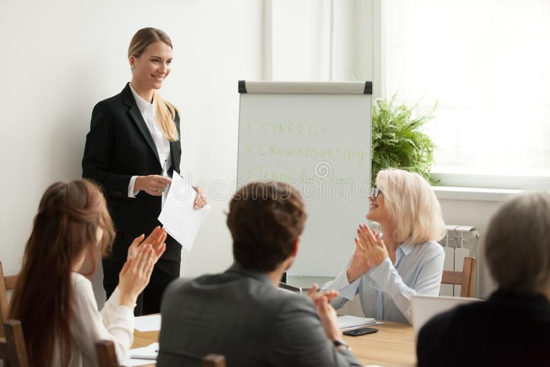 Executive team congratulating successful female manager with app. Executive business team congratulating successful female manager with applause at conference royalty free stock photos