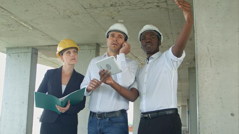 Executive team on construction site discussing project, using smartpone and digital tablet stock photo