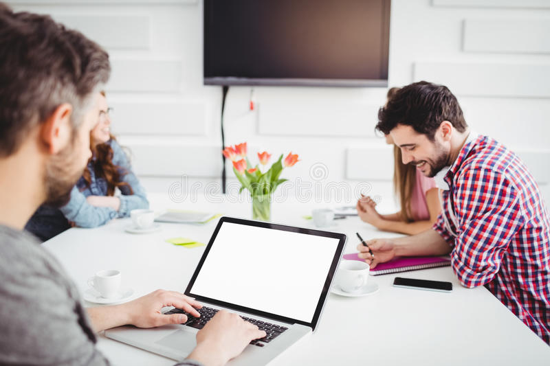 Executive using laptop in meeting at creative office stock image