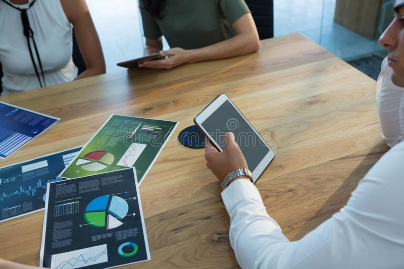 Executive using tablet with business graph on table stock photos