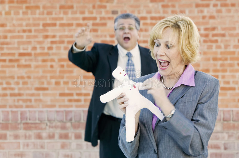 Executive Voodoo. Executive pokes a pin into a Voodoo doll representing her boss or coworker stock photos
