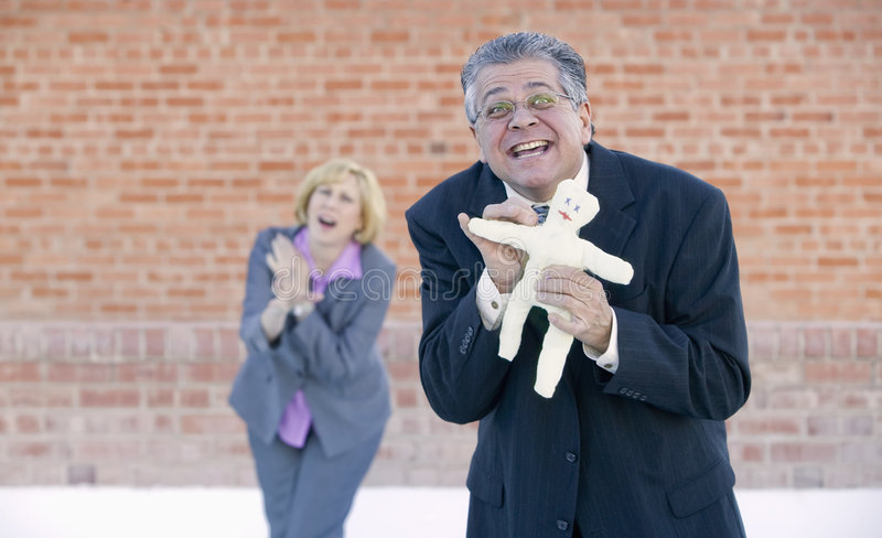 Executive Voodoo. Executive pokes a pin into a Voodoo doll representing her boss or coworker stock images