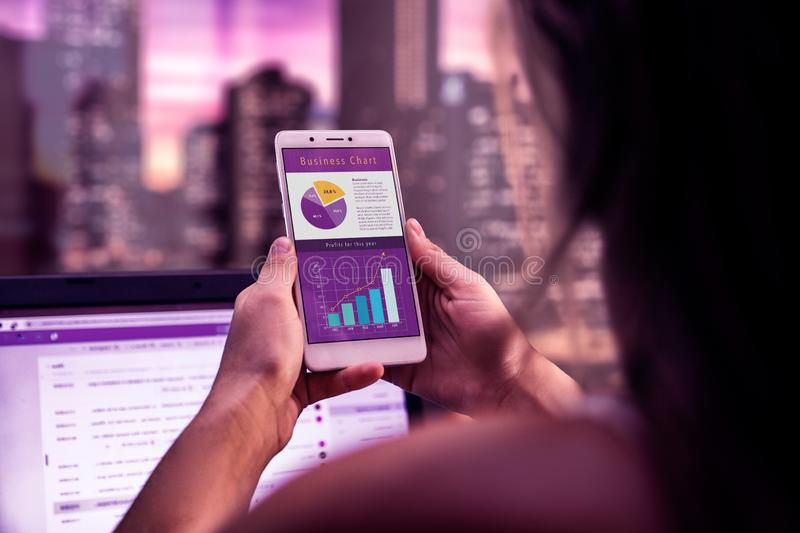 Executive woman on a desk with cell phone in her hands. A business app on the screen of smartphone. Working at night. Application. Marketing, profits graphs stock image