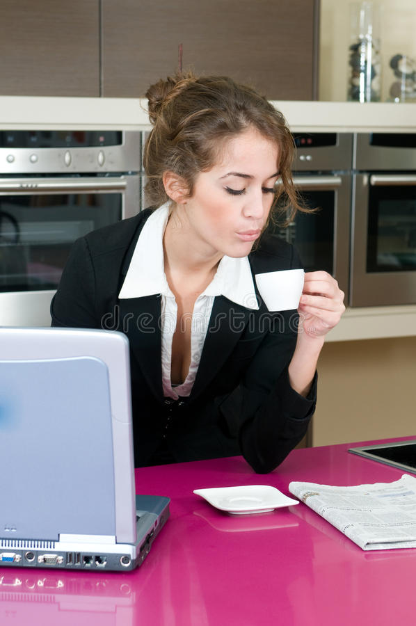 Executive woman in kitchen coffee looking laptop stock images