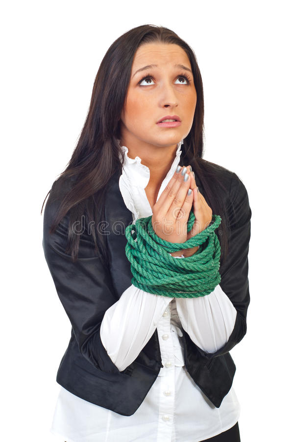 Executive woman with tied hands praying. Young executive woman with hands tied praying and looking up isolated on white background royalty free stock image
