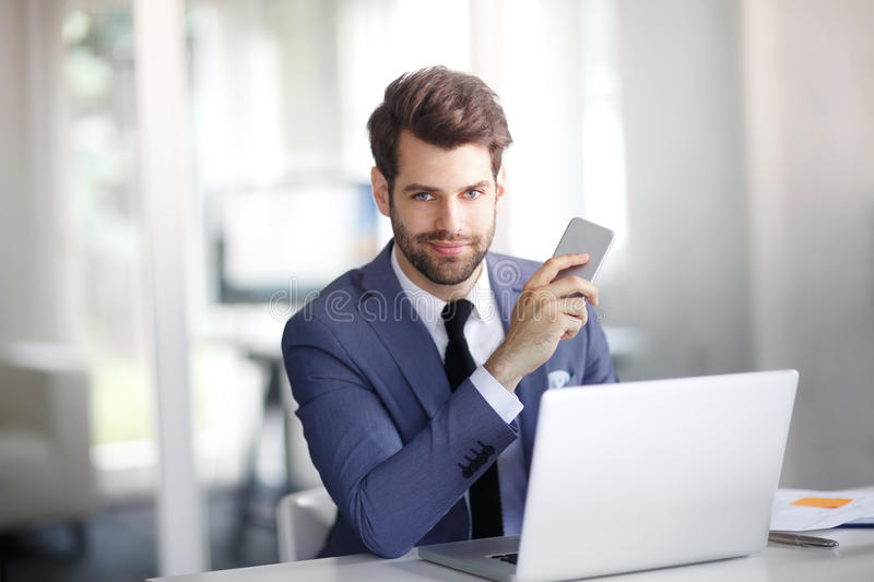 Executive young professional man. Portrait of young businessman working on laptop and using his smartphone while sitting at office royalty free stock image