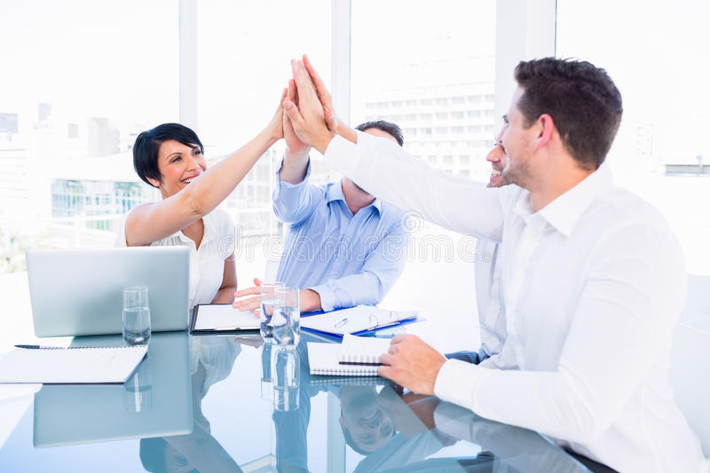 Executives giving high five in a business meeting. Smartly dressed young executives giving high five in a business meeting at office desk stock image