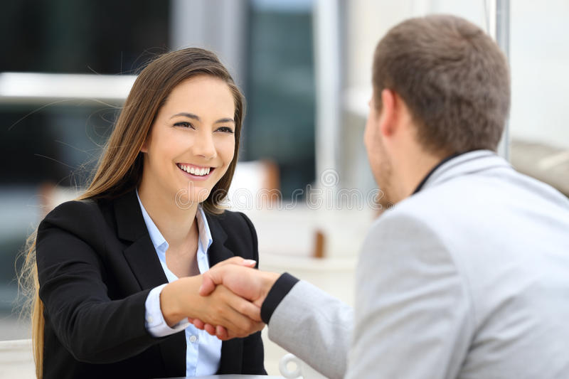 Executives handshaking in a coffee shop. Two executives meeting and handshaking sitting in a coffee shop stock images