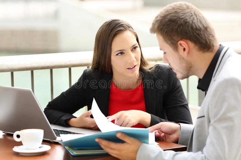 Executives having a business conversation in a bar. Two executives having a business conversation sitting in a coffee shop royalty free stock photos