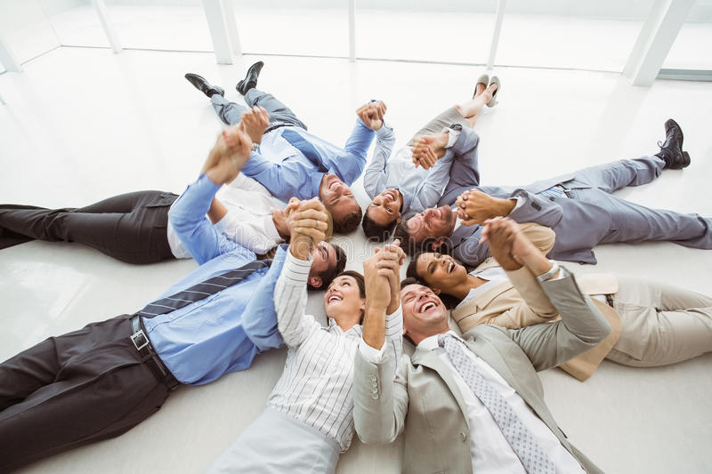 Executives holding hands together in circle stock image