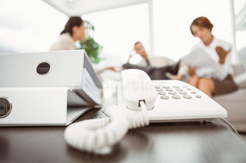 Executives with land line phone and folders in foreground. Young business people with focus on land line phone and folders stock photos