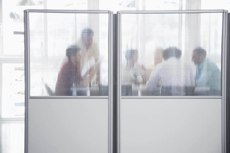 Executives In Meeting Behind Translucent Wall. Group of business people in meeting behind translucent wall in office royalty free stock images