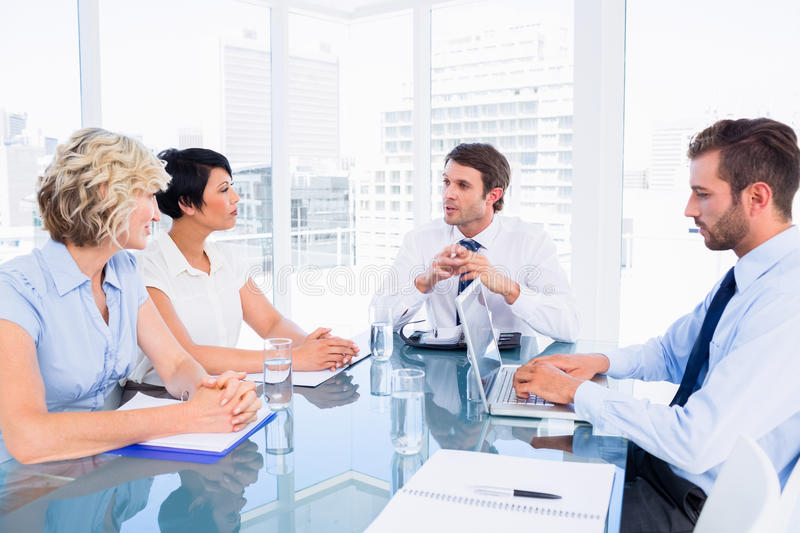 Executives sitting around conference table. Smartly dressed young executives sitting around conference table in office stock image