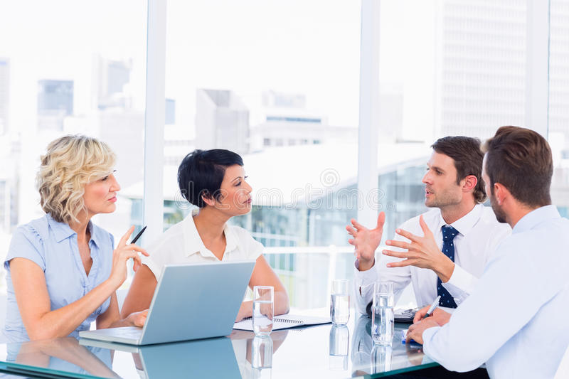Executives sitting around conference table. Smartly dressed young executives sitting around conference table in office stock images