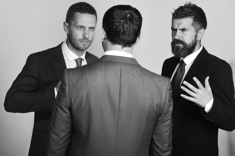 Executives trying to find compromise on light grey background. Men with beard and convictive faces discuss leadership. Business Argument and business concept royalty free stock photos