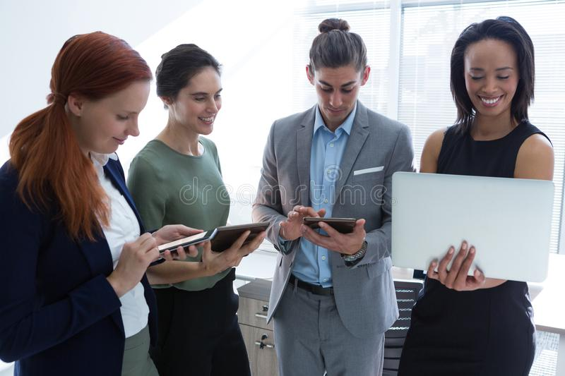 Executives using mobile phone, laptop and digital tablet in the office stock photo
