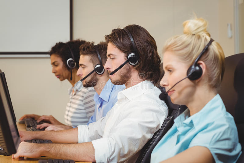 Executives working in call center. Wearing headsets royalty free stock photo
