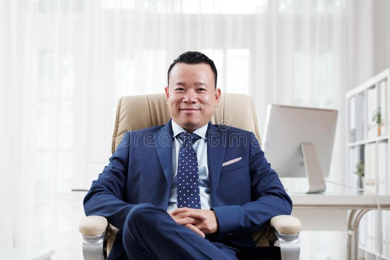 Executivo asiático que senta-se no escritório imagens de stock royalty free