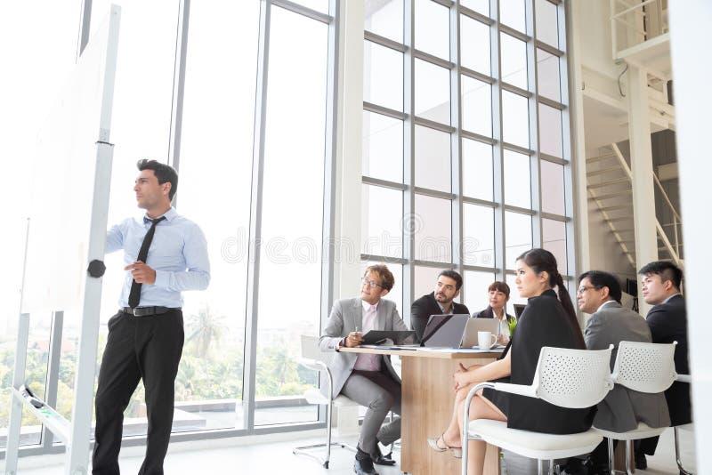 Executivo de negócios apresentando seus colegas durante a reunião imagens de stock royalty free