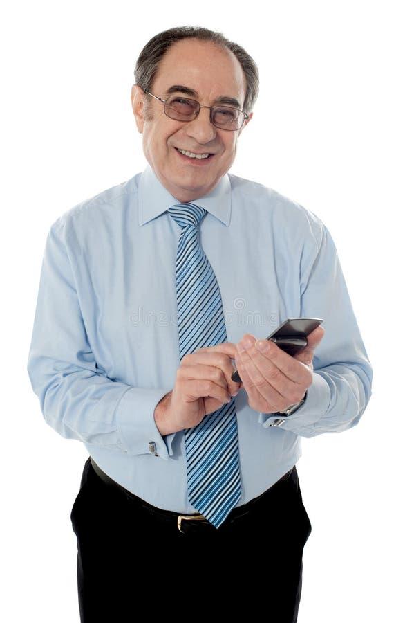 Executivo empresarial mais idoso de sorriso que texting foto de stock royalty free